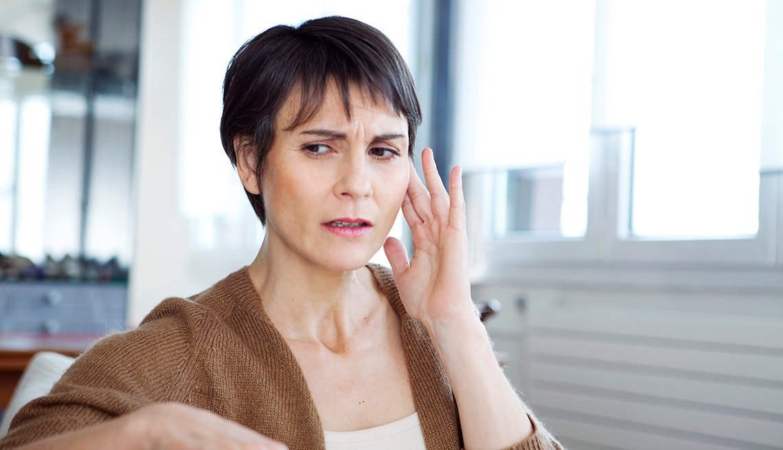 A woman places her fingers near her ear as she suffers discomfort from tinnitus