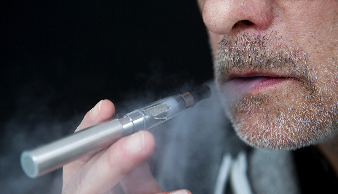 Hombre mayor fuma un cigarrillo electrónico