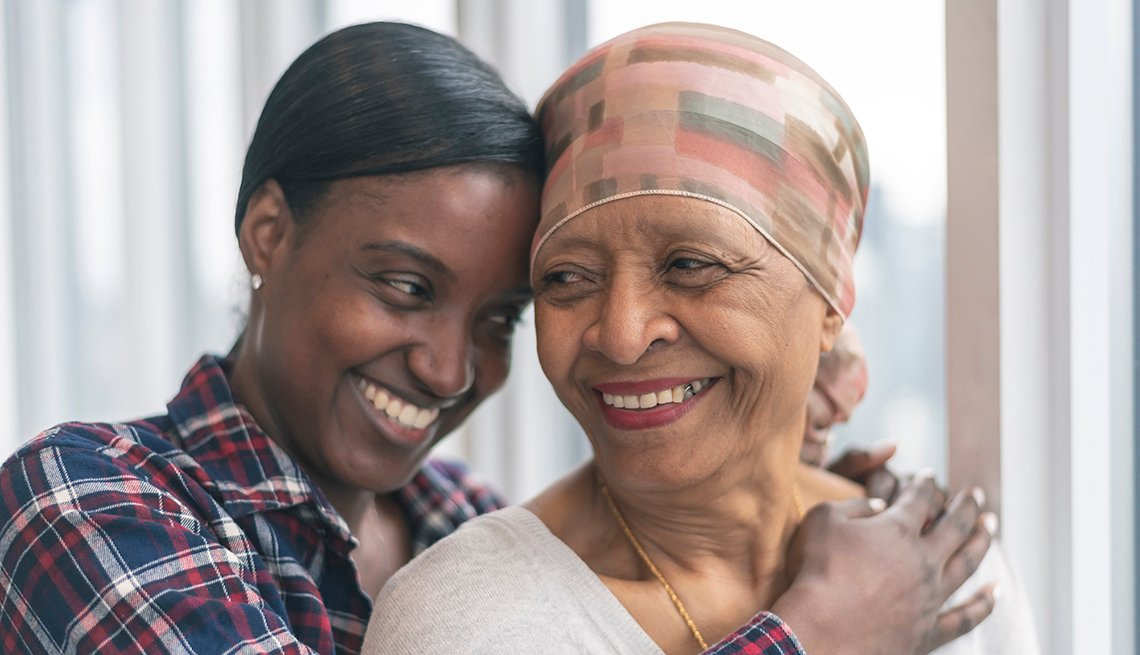 A woman with cancer is wearing a scarf on her head as her adult daughter is giving her a hug. Both women are smiling with gratitude and hope for recovery.
