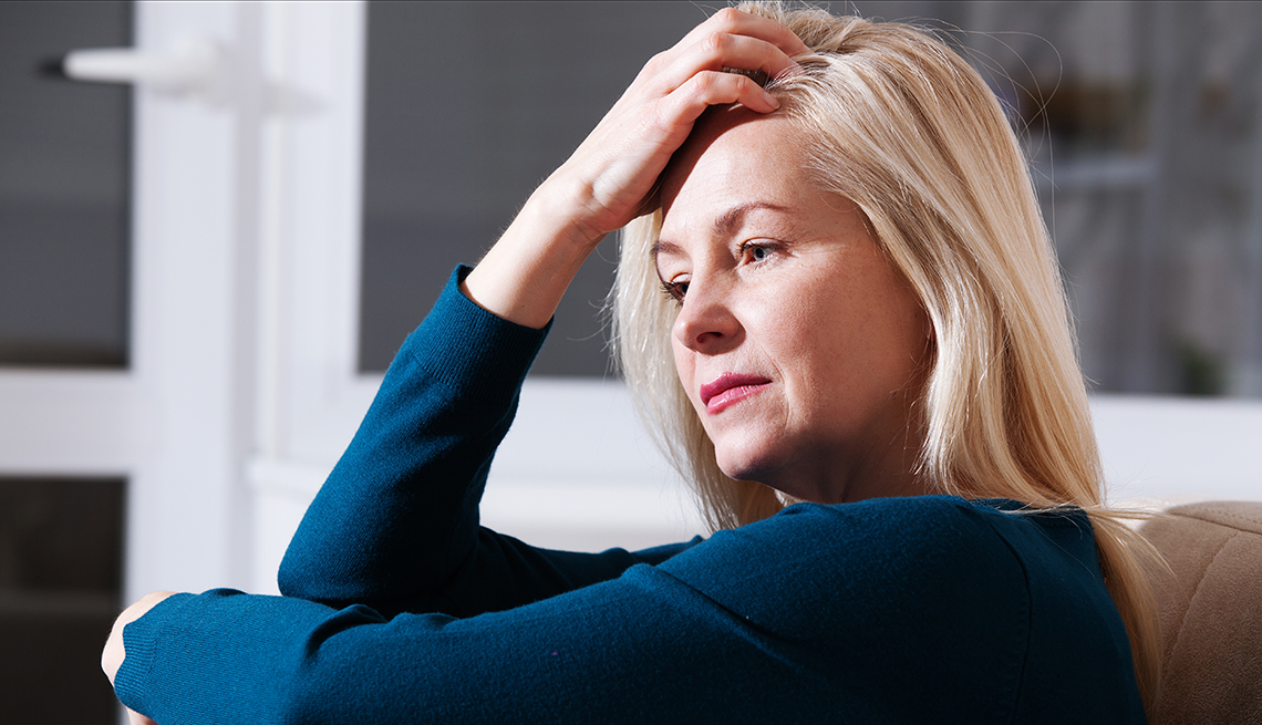 A sad woman at home sitting on the couch, looking down and touching her forehead
