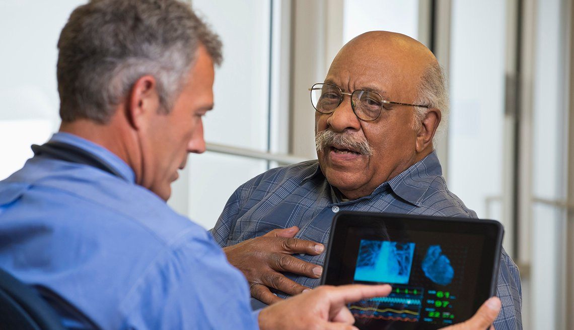 A doctor is talking to patient about his heart while using a digital tablet