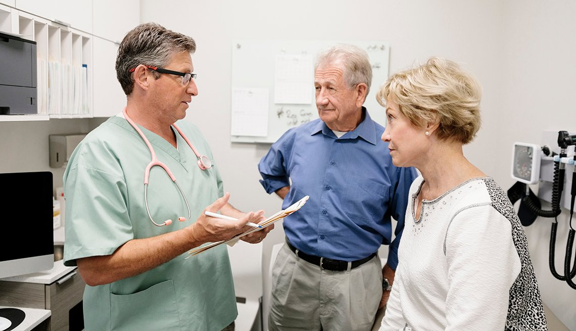 A doctor is speaking to a couple in an examination room