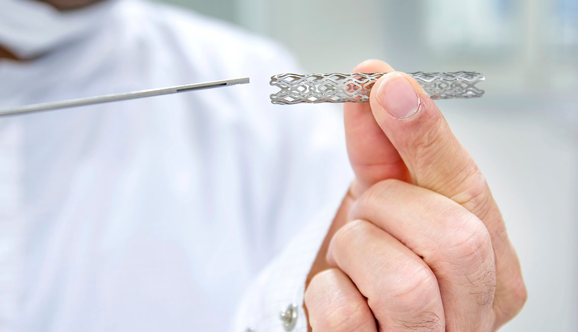 A man holding a heart stent in his hand