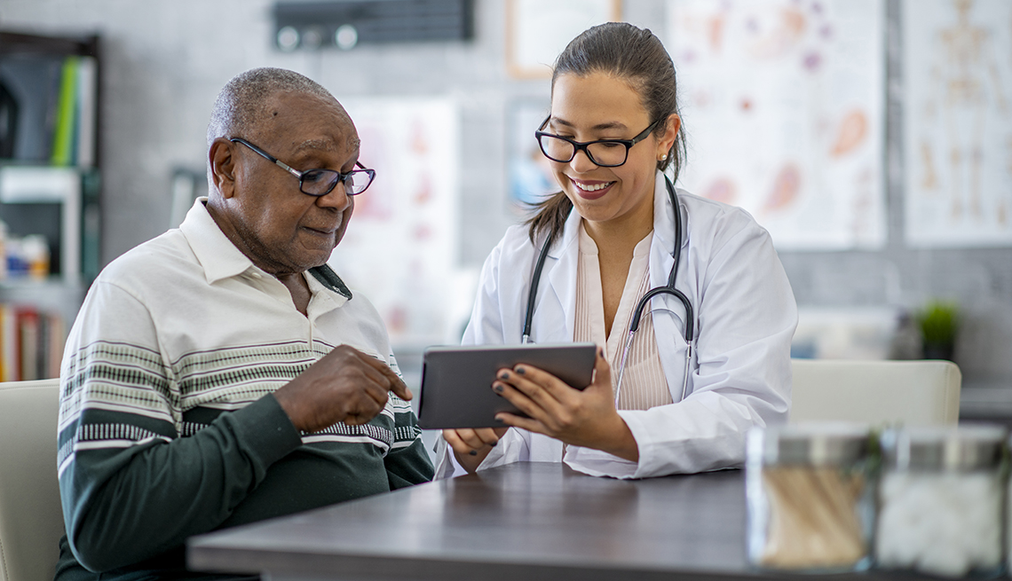 A man is sitting in his doctor's office and listening as the doctor shows him something on a digital tablet