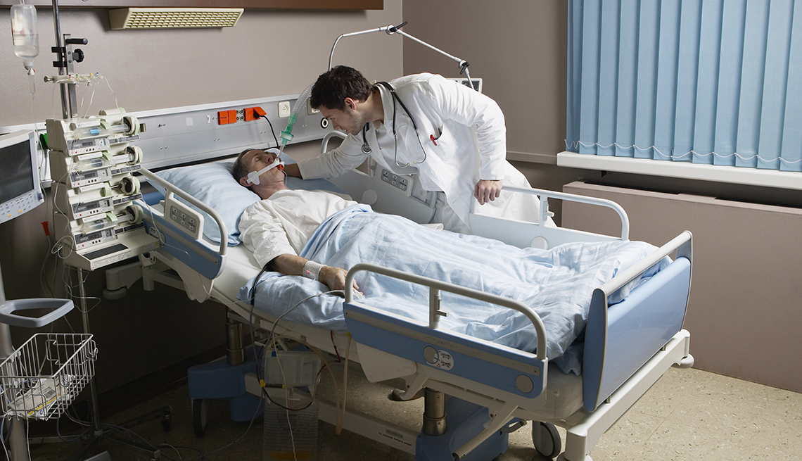 doctor examines a seriously ill patient in an hospital bed