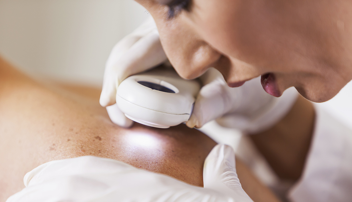 Female dermatologist examining patient's skin with dermascope for signs of skin cancer.