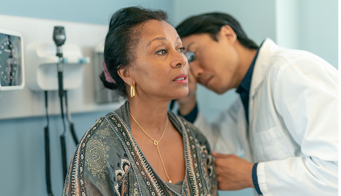 Woman has ears checked by doctor in medical office