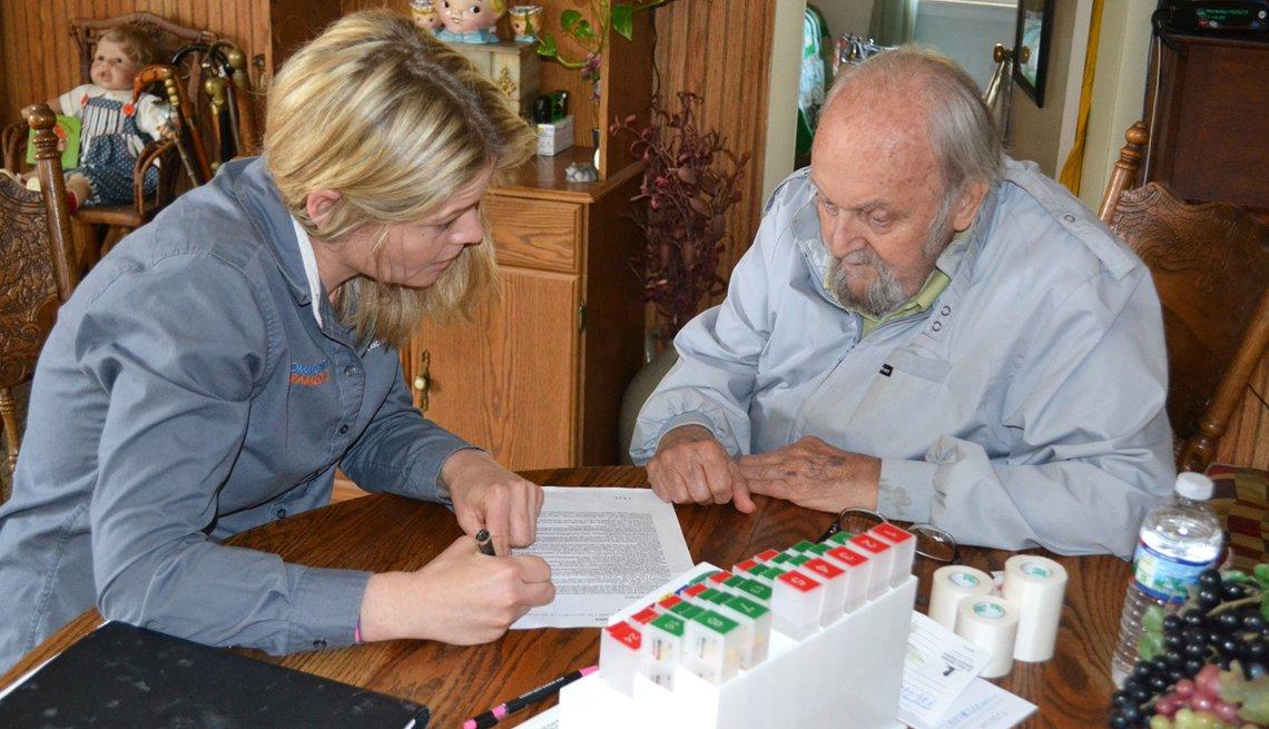 Un paramédico asiste a una persona en su hogar.