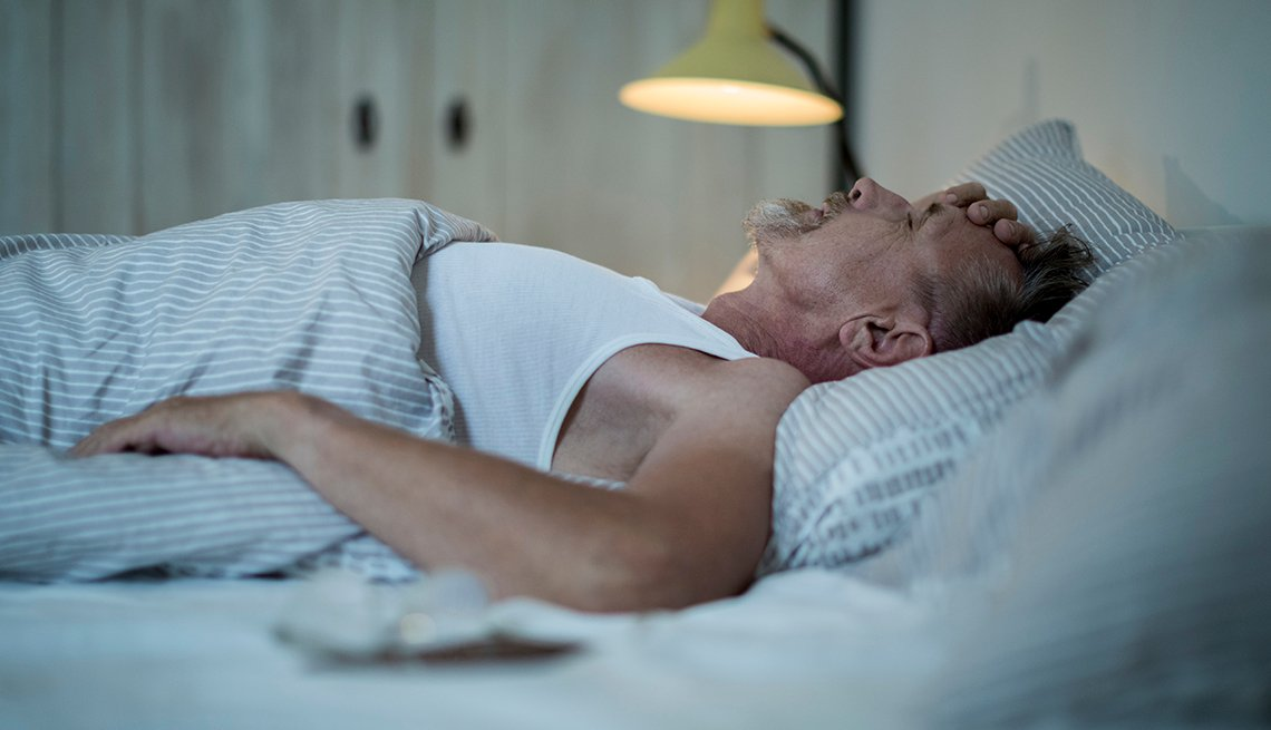 An older man is lying in bed holding his head.