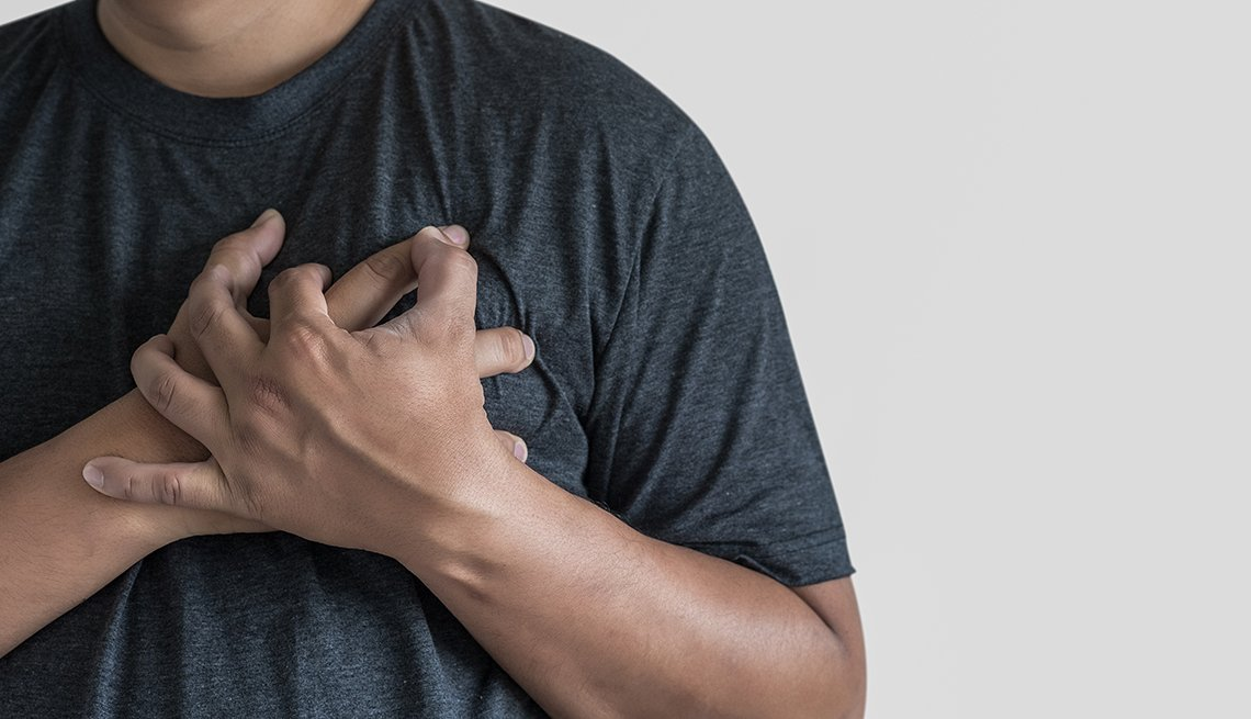 A man places his hands on his chest suffering from apparent pain from his heart