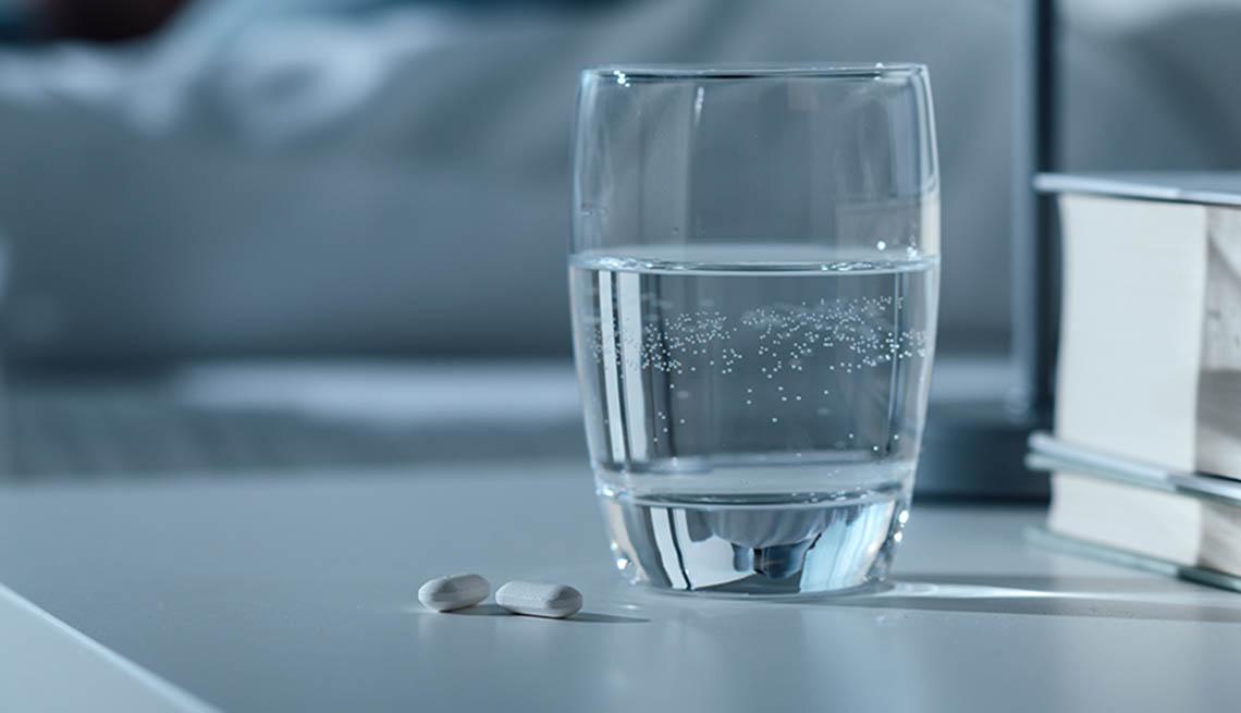 Vaso con agua y pastillas sobre una mesa de noche