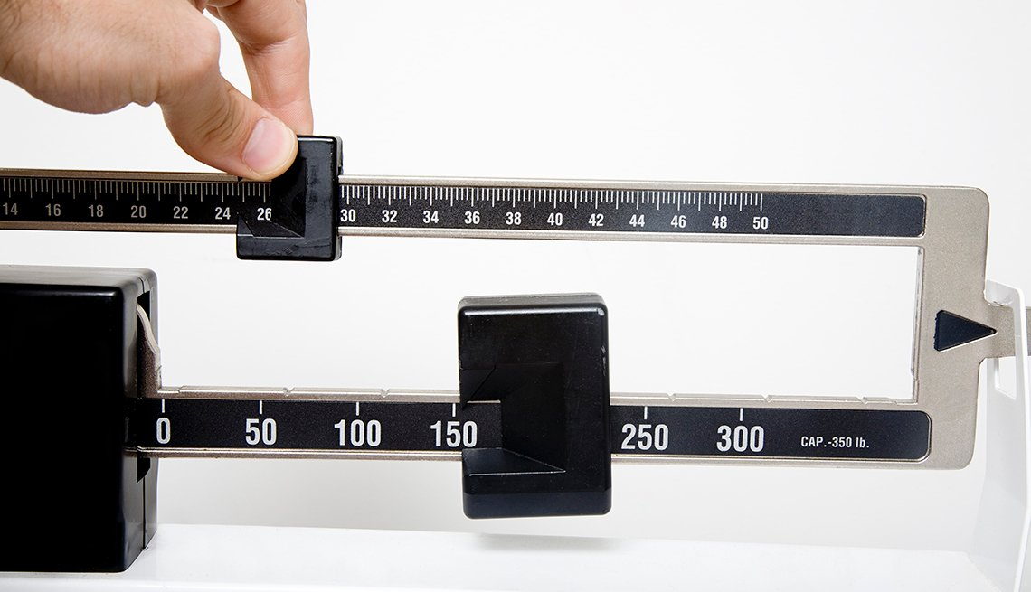 A stand up doctor's office style scale with a hand calculating the weight