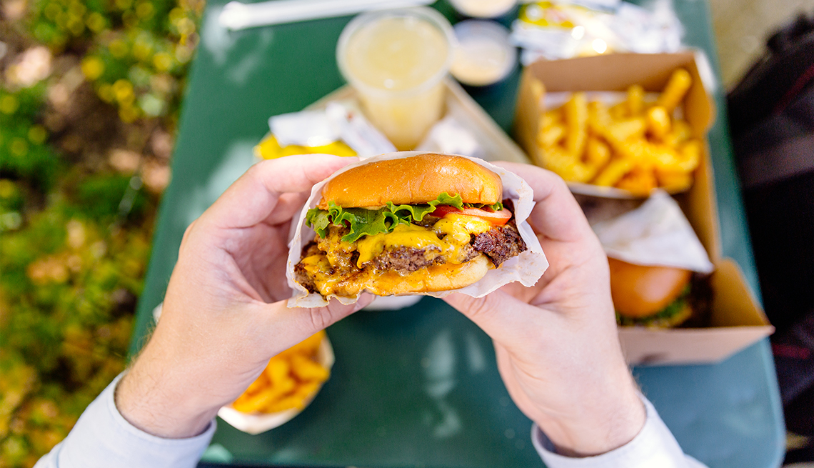 A personal perspective view of a man holding a cheeseburger over a table