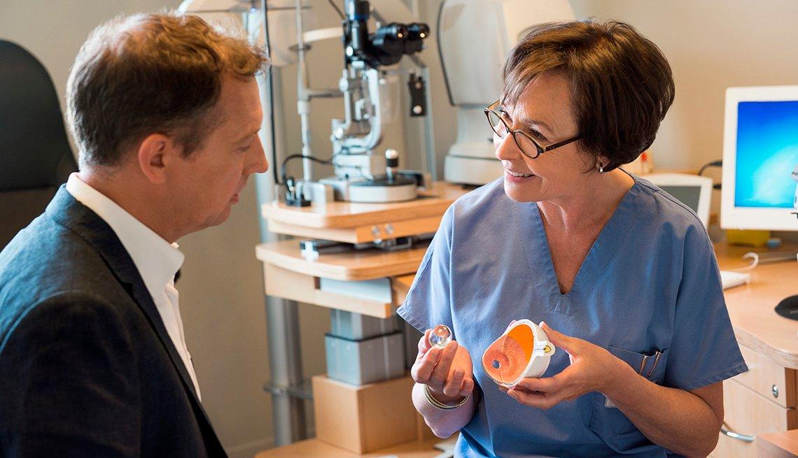 Una optómetra le muestra un modelo de un ojo a un paciente