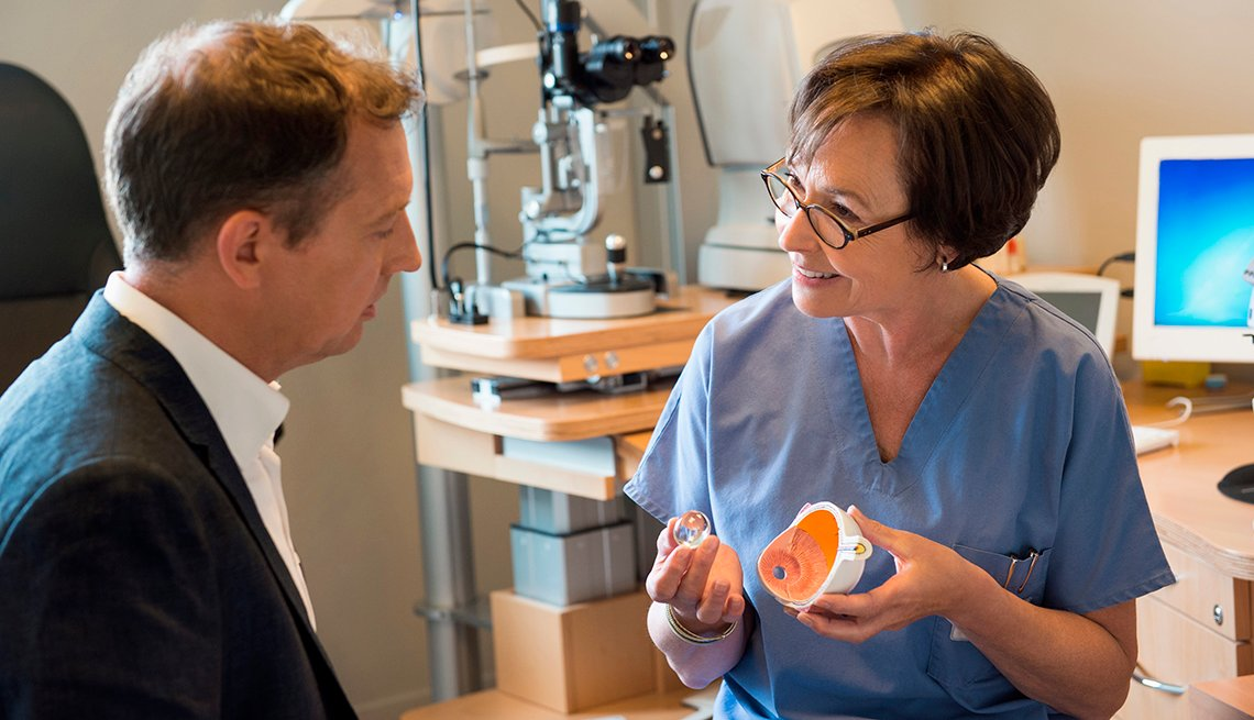 A female optometrist showing a model of an eye to a male patient