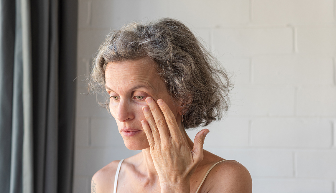 A woman with grey hair rubbing her eye to wipe away tear