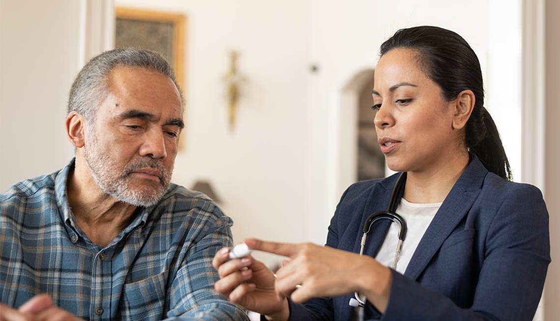 A Hispanic female doctor is talking to her senior male patient during a home medical visit. She is showing him how to use a diabetes kit.