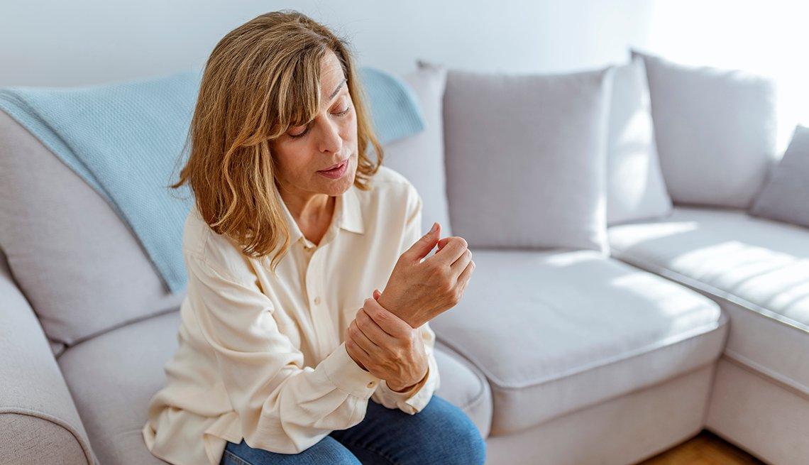 Una mujer se agarra la muñeca en señal de dolor