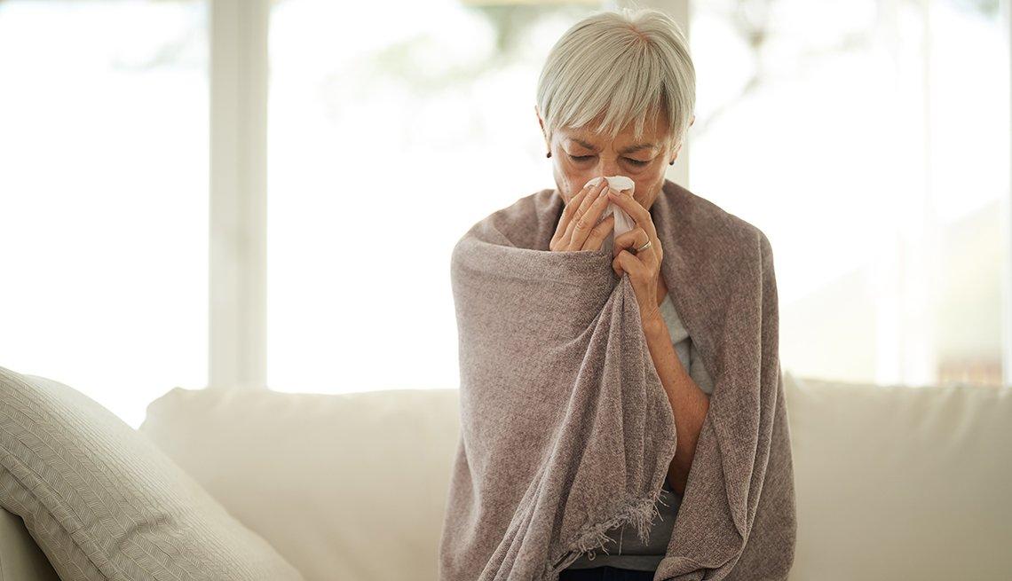Una mujer con resfriado se limpia la nariz y está arropada con una manta