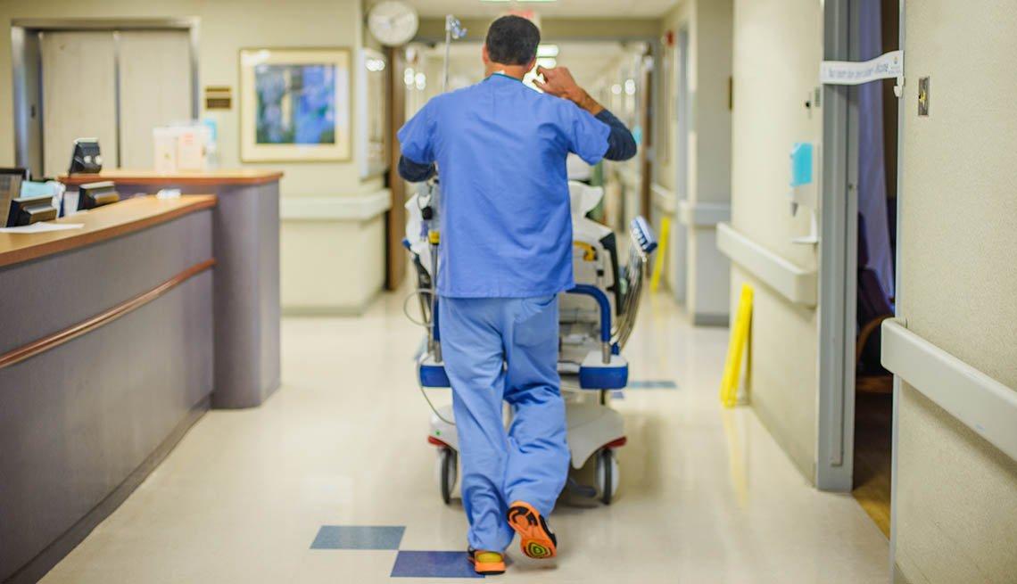 Un empleado de un hospital lleva una camilla por un pasillo