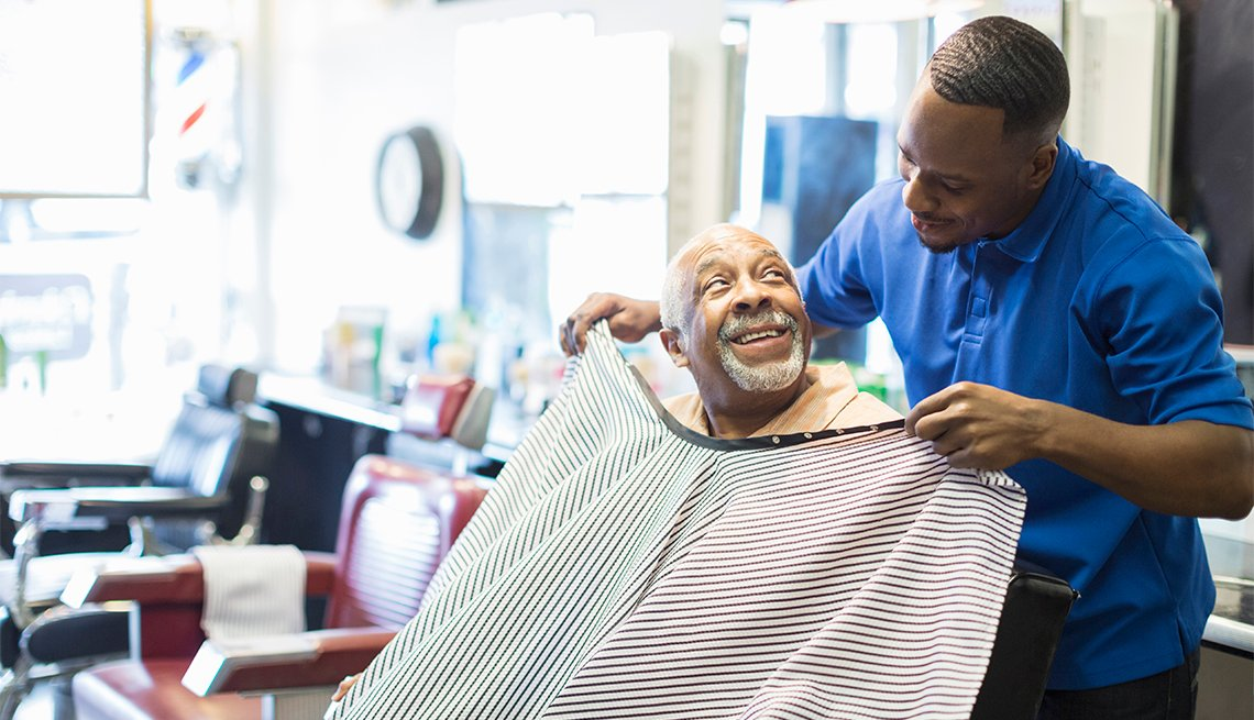 barber tying apron on customer in retro barbershop
