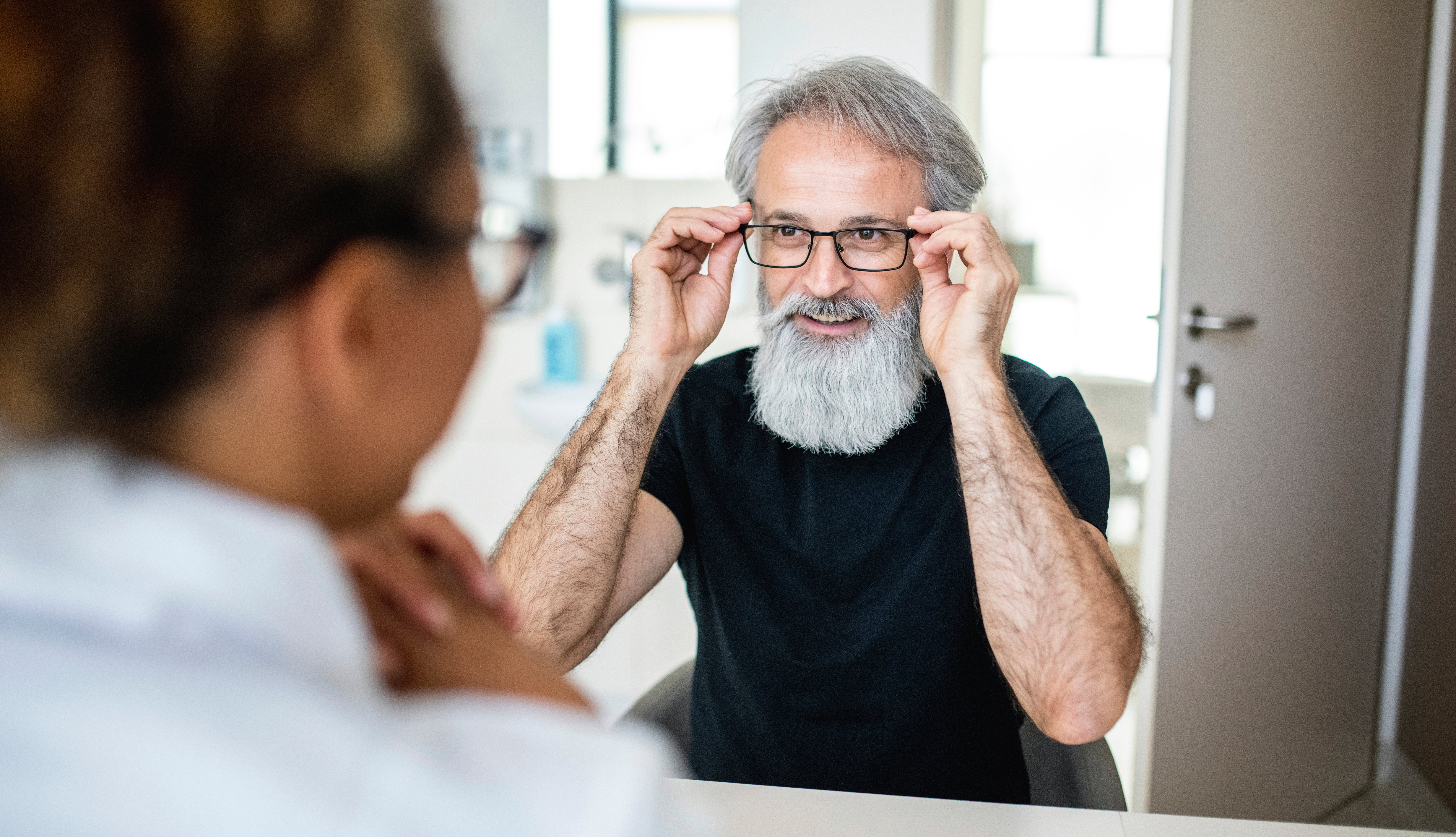 man at optometrist office trying on new glasses