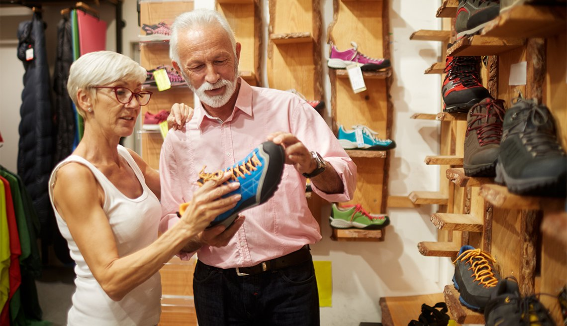 Senior couple in sports and outdoor equipment store choosing hiking shoes.