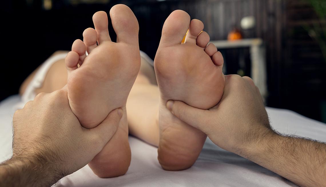 A massage therapist does a foot massage.