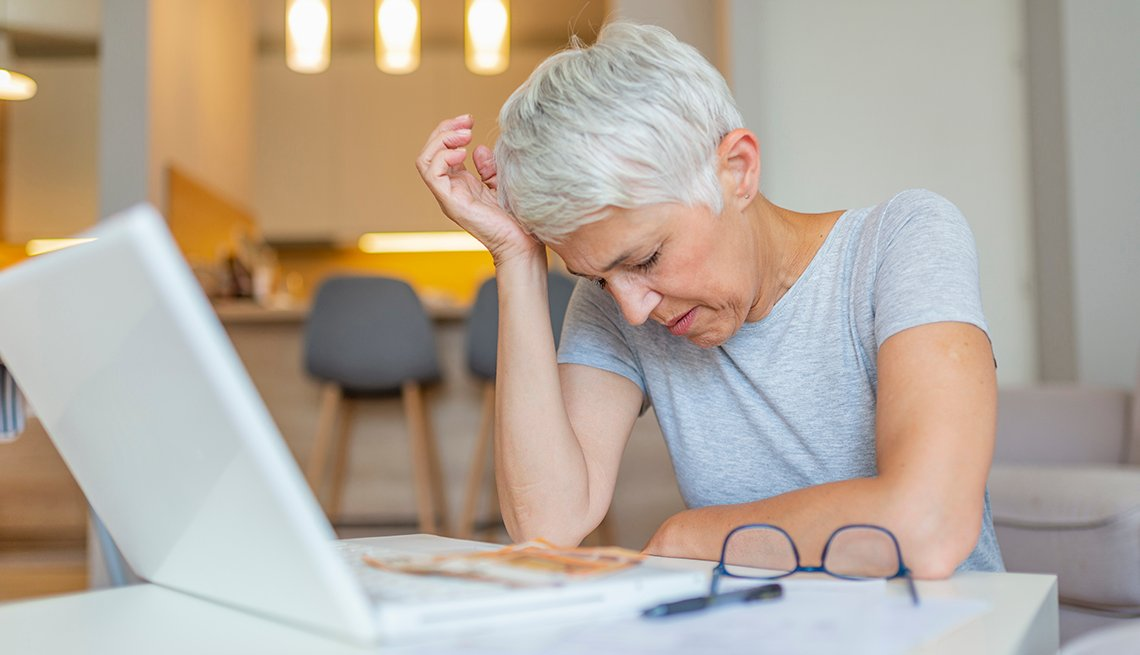 Frustrated older woman at computer looking at a bill