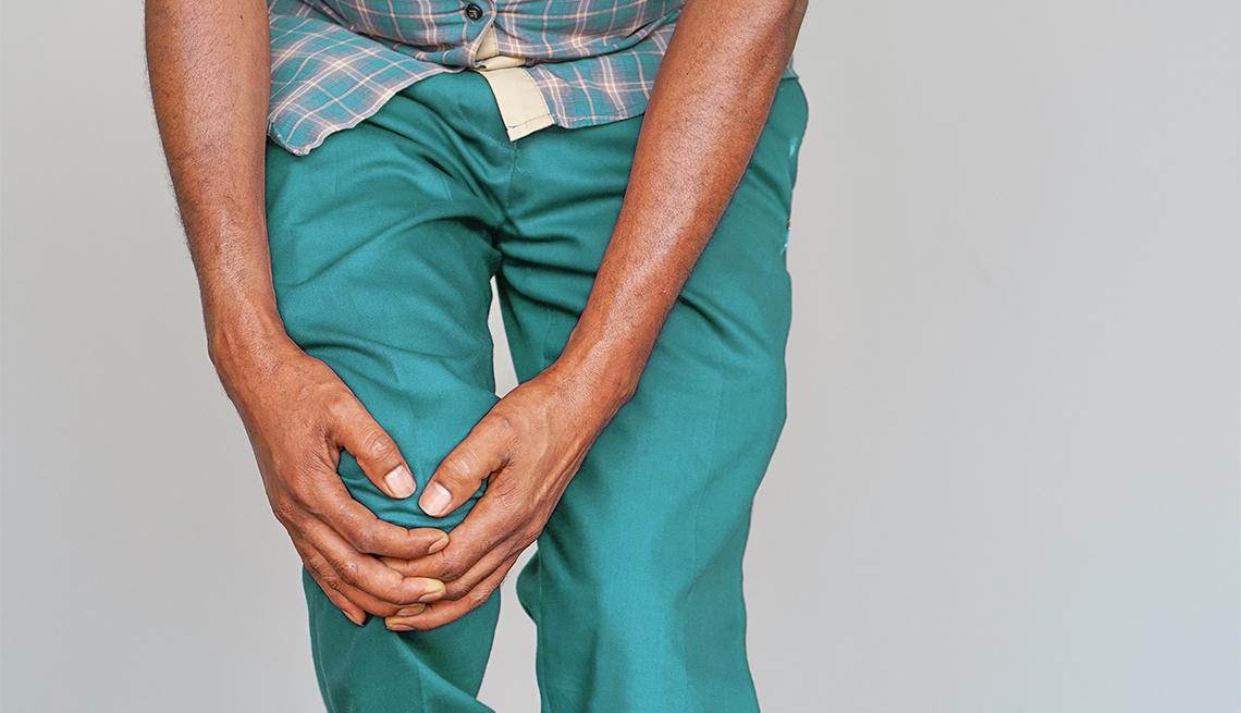 Un hombre se agarra una rodilla con ambas manos