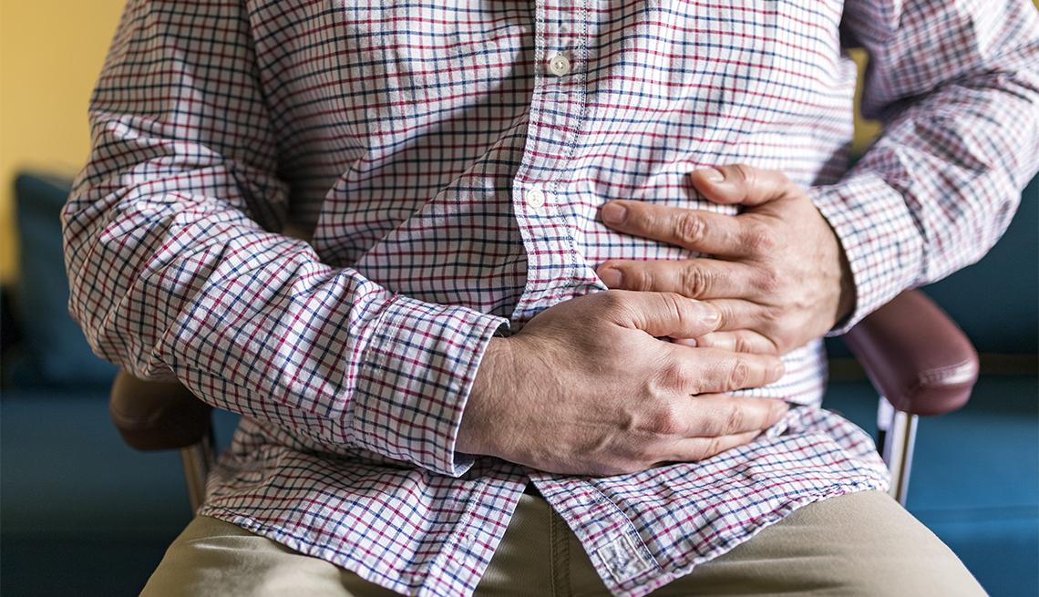 Hombre con sus manos en el abdomen en señal de dolor