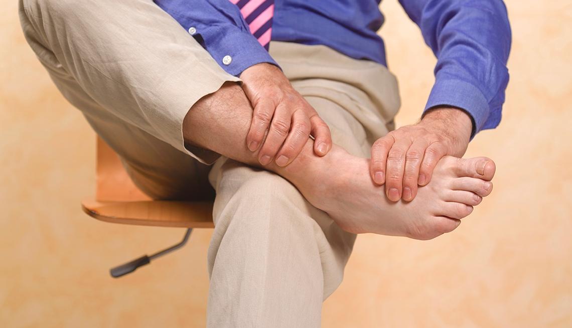 Man in chair rubbing his bare feet