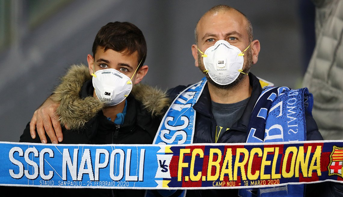 two soccer fans wear medical face masks while attending a match on february 25 2020 in naples italy