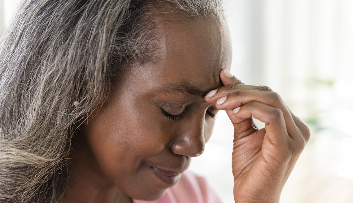 Older African American woman holding her brow as if she has a headache