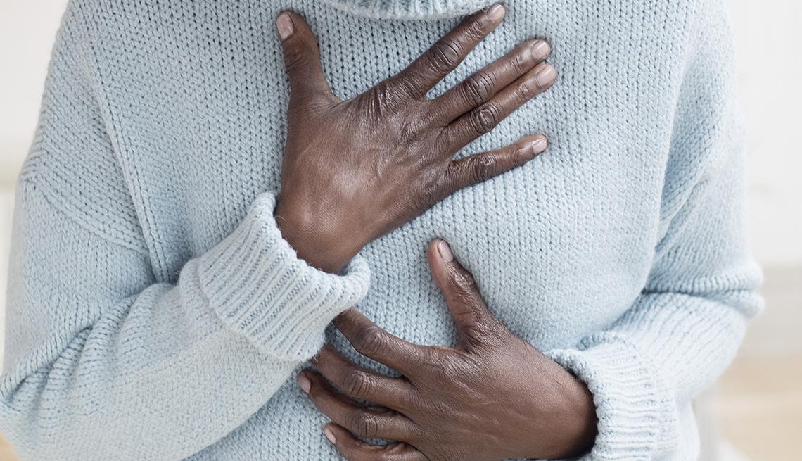 Una mujer se lleva la mano al pecho en señal de dolor.
