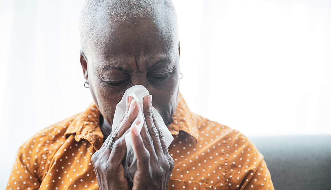 Senior Black woman holding a tissue, wiping her nose