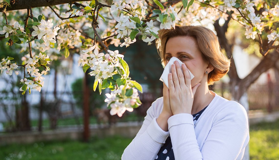 woman with pollen allergies standing outdoors under blossoming trees sneezing into a tissue