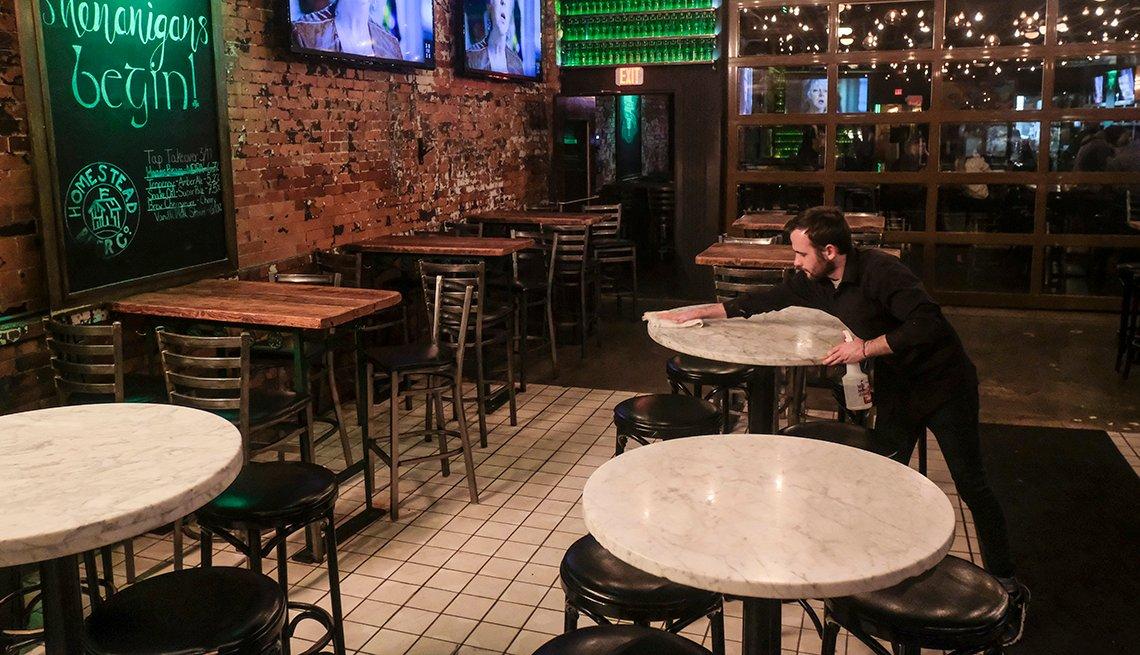 A waiter cleans a table at a bar