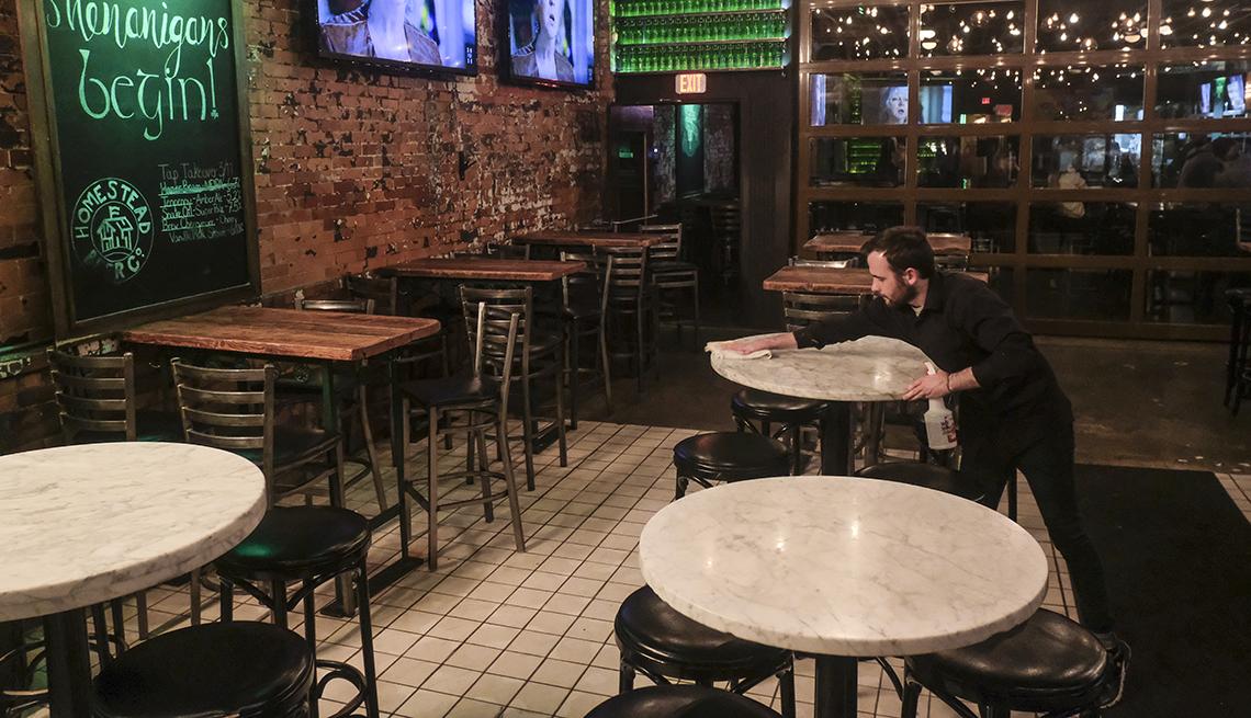 Mesero limpia la mesa en un restaurante vacío