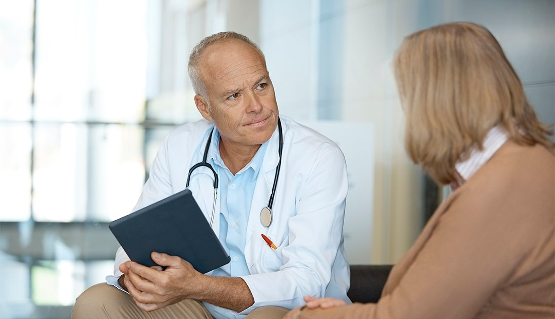 Serious doctor looking at woman while holding digital tablet.