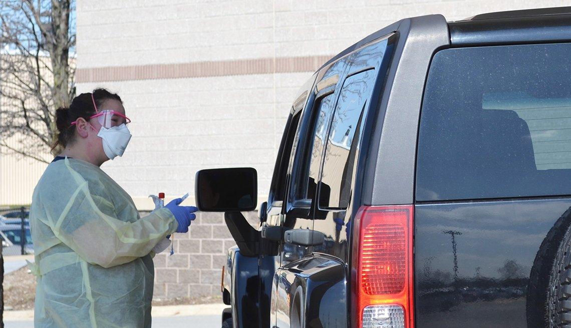 La enfermera Jennifer Homan asiste a una persona en su auto durante el brote de coronavirus