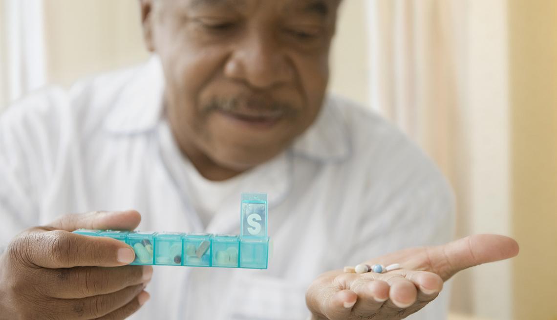 Un hombre sostiene una caja plástica con sus pastillas diarias