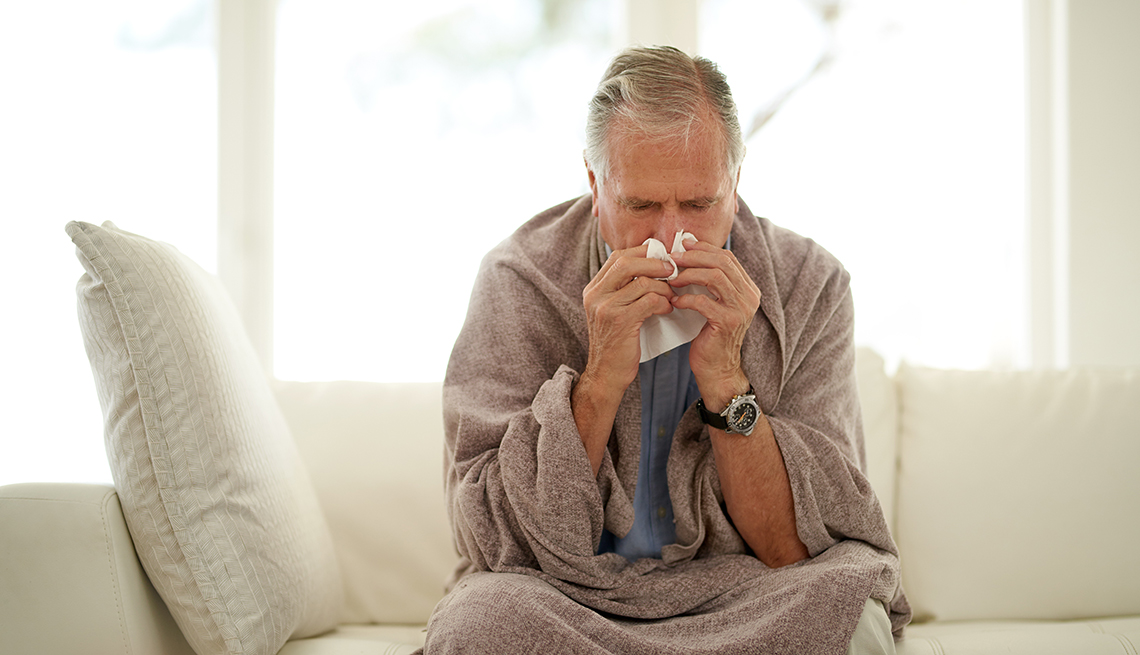 Shot of a senior man blowing his nose with a tissue at home
