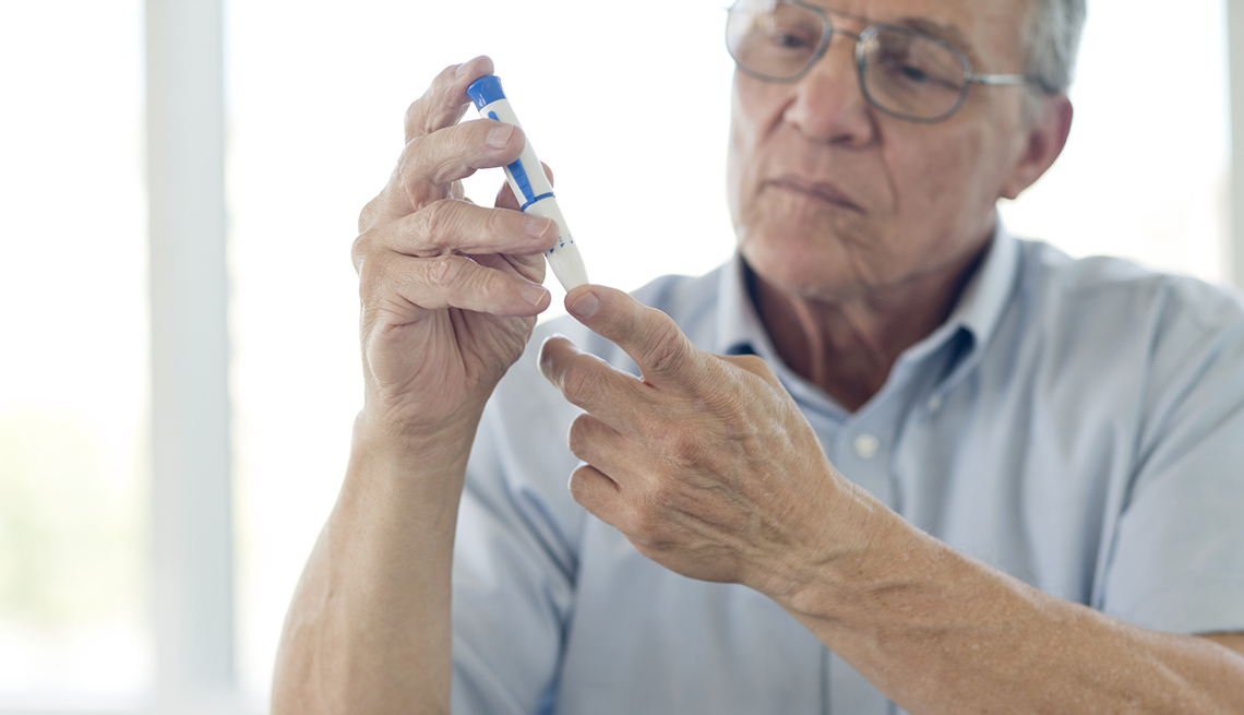 Hombre mayor haciendo una prueba de azúcar en un dedo.