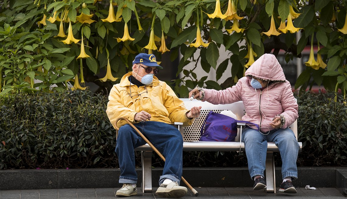 People wearing protective masks use hand sanitizer while sitting in Union Square in San Francisco, California, U.S., on Wednesday, March 4, 2020.