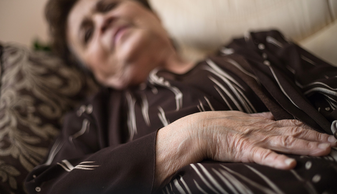 Mature woman is lying on the sofa in pain with stomach problems