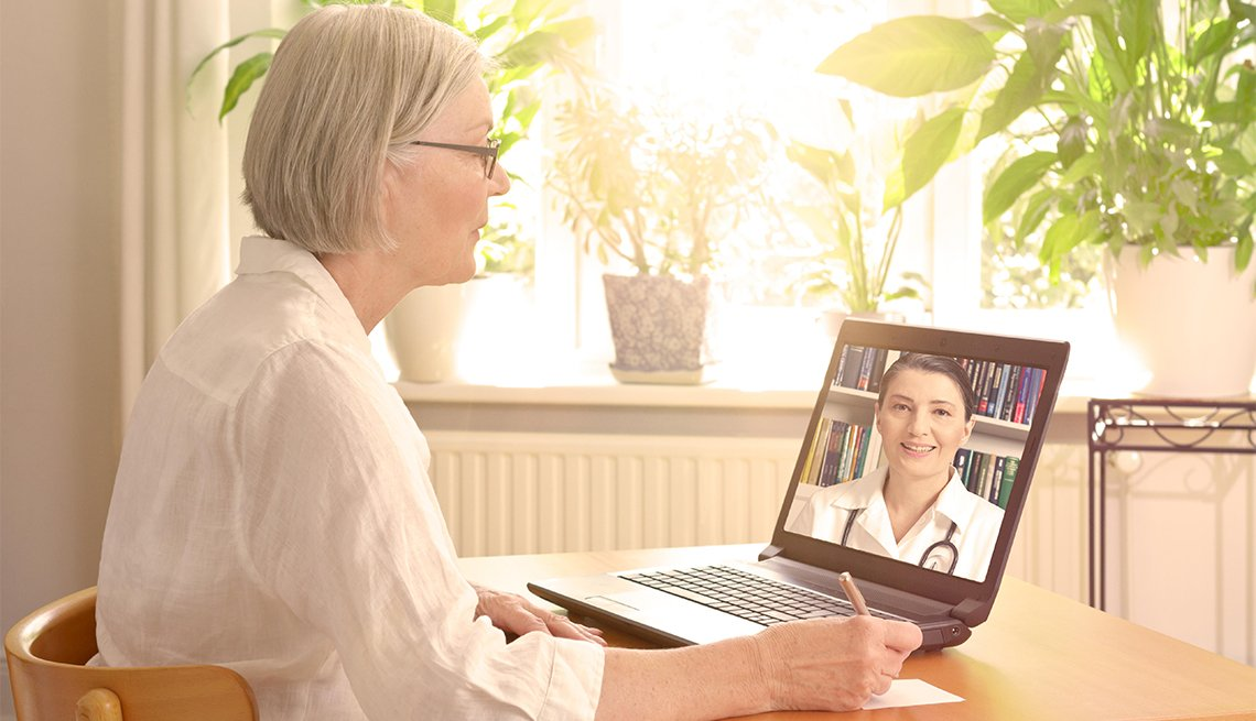 Woman in front of a laptop taking  notes during a video call with her female doctor