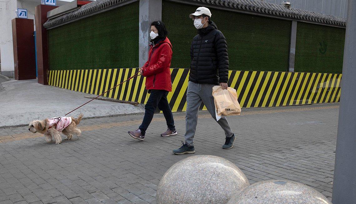 Una pareja usando mascarillas camina su perro