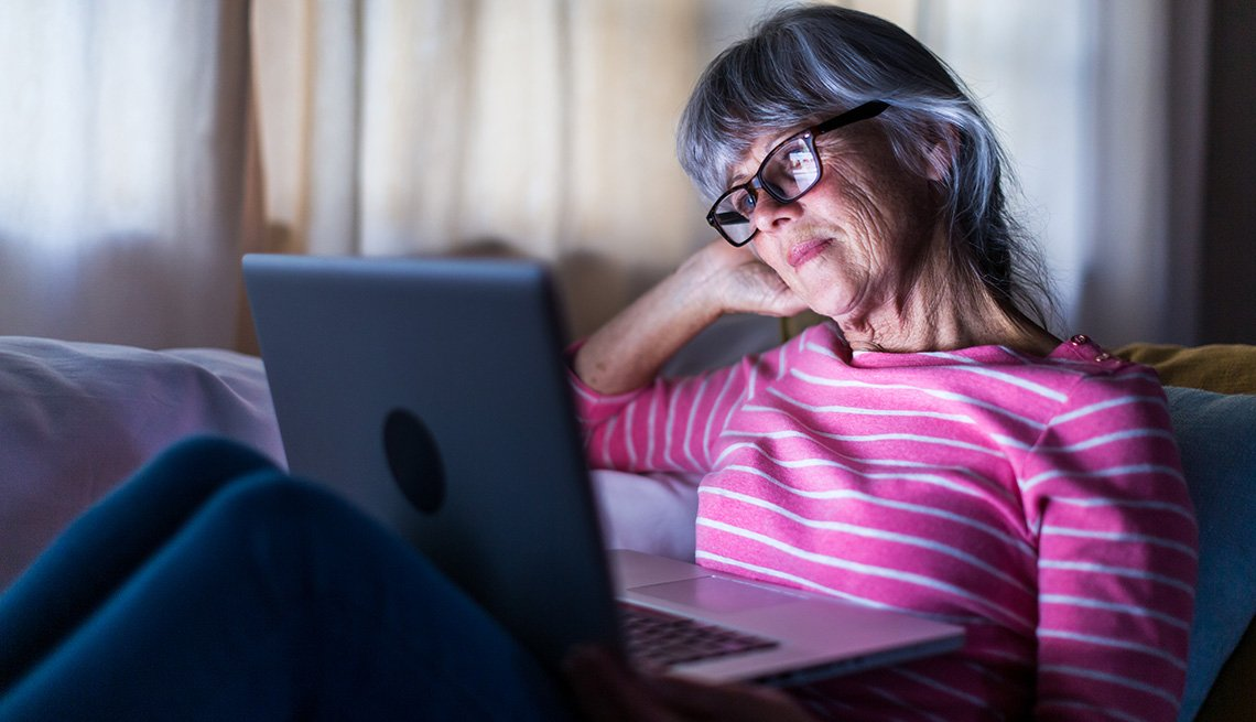 Una mujer mira su computadora portátil sentada en un sofá