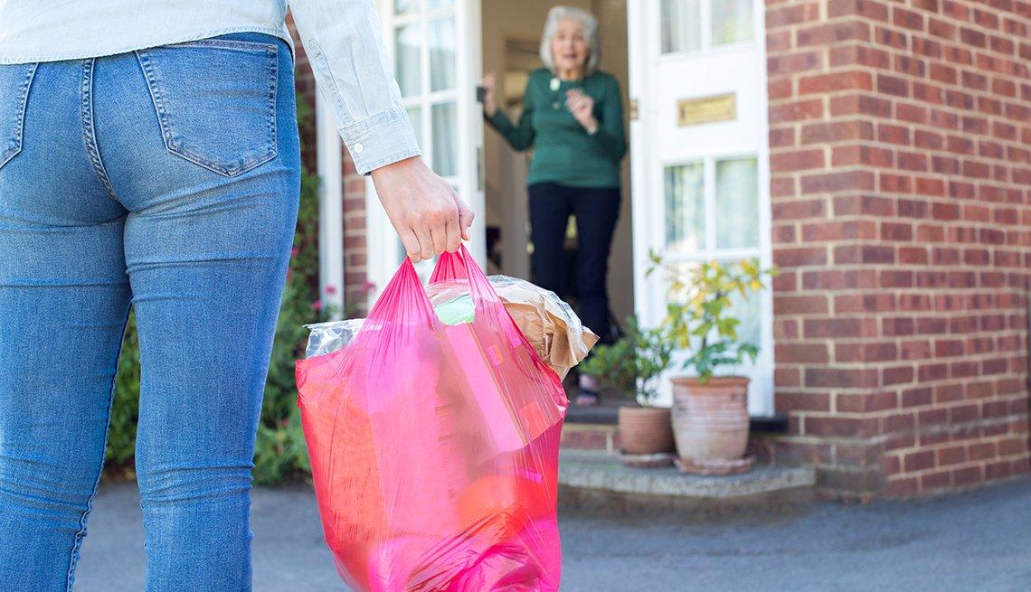 Una mujer le lleva un bolso de alimentos a una mujer mayor que la recibe en su casa